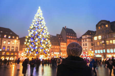 People in christmas market, woman looking at the decorated illuminated tree, festive new year lights in Strasbourg, France, Europe