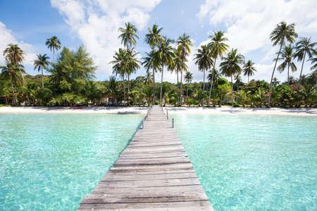 Paradijsstrand met turkoois water, houten pijler en tropische palmen, de zomervakantie in Thailand, Koh Kood Stockfoto