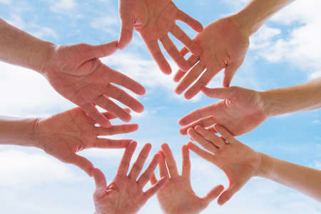 Team or brotherhood concept, group of people putting hands together against blue sky Фото со стока