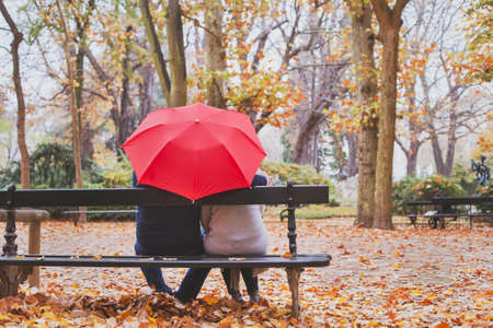 Elderly retired couple sitting together on the bench in autumn park, love concept Stock Photo