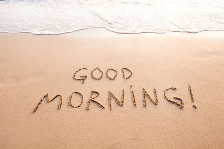 Good morning, message text concept card, text written on sand beach
