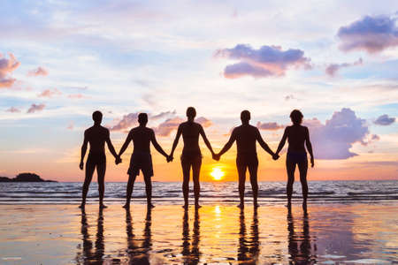 community or group concept, silhouettes of people standing together and holding hands, team on the beach, unity background Stock Photo