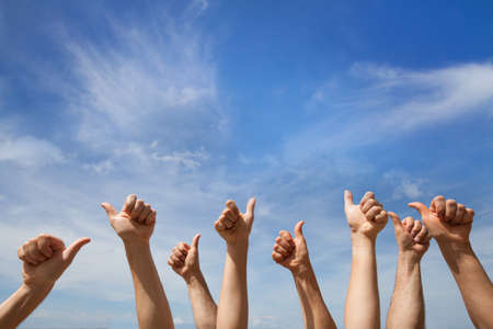 Like concept, many hands showing thumb up or ok sign on blue sky background Standard-Bild