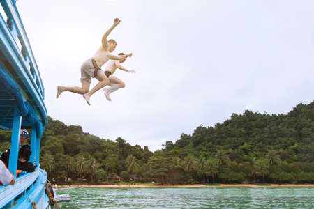 friends jumping to the sea from boat, having fun together, beach tropical adventure, adrenaline