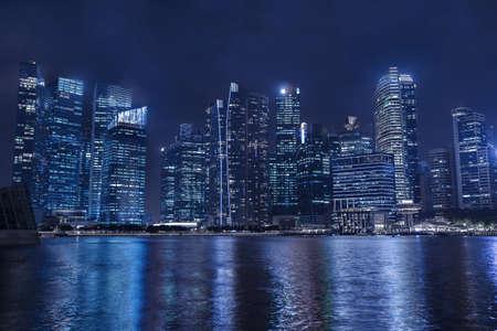 夜、ビジネス高層ビル、事務所ビル反射水で近代的な都市のスカイライン 写真素材
