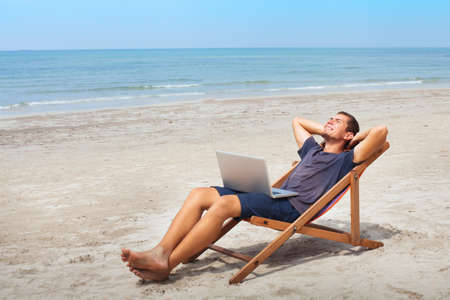 Freelancer with laptop on the beach, successful happy business man relaxing, freelance work