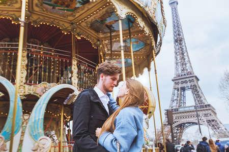 Gelukkig koppel in Parijs, romantische kus dichtbij de carrousel en de Eiffeltoren