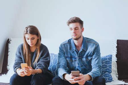 Jaloerse man man spionerende vrouw, verdachte vriend probeert berichten te lezen op de mobiele telefoon van zijn vriendin terwijl ze niet kijkt Stockfoto