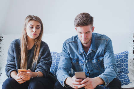 Mujer celosa esposo espía, novia sospechosa tratando de leer mensajes en el teléfono móvil de su novio, mientras que no está viendo Foto de archivo - 77409571