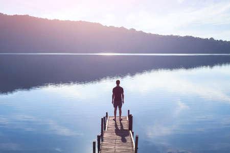 Soñador, silueta, de, hombre, posición, en el lago, madera, muelle, en, ocaso, fuerza humana, psicología, concepto