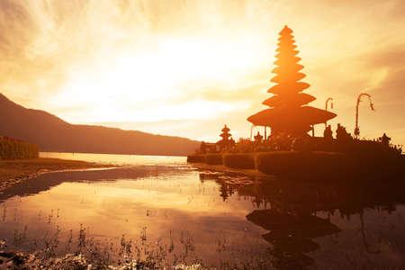 バリ島、インドネシアの美しい伝統的な建築のプラ ・ ウルン ・ ダヌ ・ ブラタン寺院の夕日 写真素材