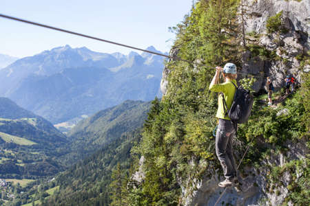 Via ferrata climbing, woman in harness crossing rope bridge in the mountains, alpinism or extreme sport