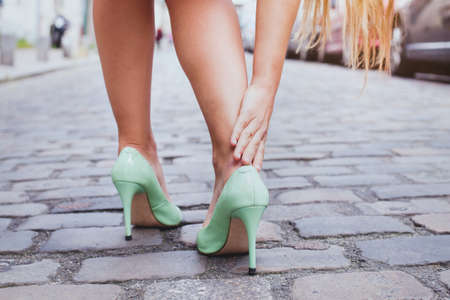 blisters, woman on high heels has difficulties to walk in her shoes