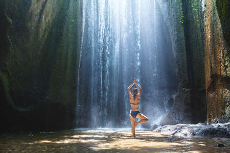 Yoga, beautiful woman practices in waterfall, body and mind harmony in the nature