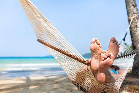 Glückliches Paar Familie in Hängematte auf tropischen Paradies Strand, Insel Urlaub, Nahaufnahme von Füßen Standard-Bild