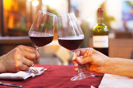 couple drinking wine in restaurant, close up of hands with glasses, happy moment