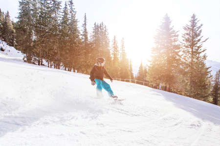 snowboarding in winter Alps, man with fast speed on snowboard in forest slope with backlight