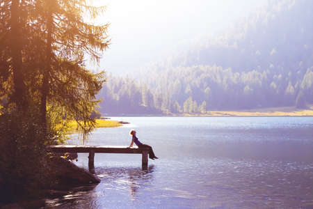 donna felice che si siede sul molo e sorridente, la felicità o il concetto di ispirazione, godersi la vita