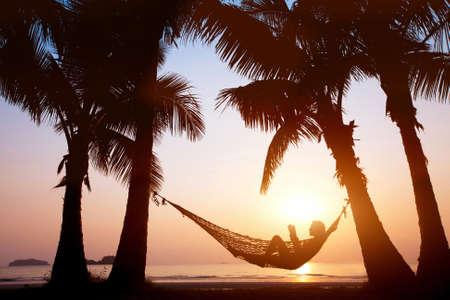 女性の美しいサンセットビーチ、ホリデイ ・ コンセプトのハンモックでリラックス