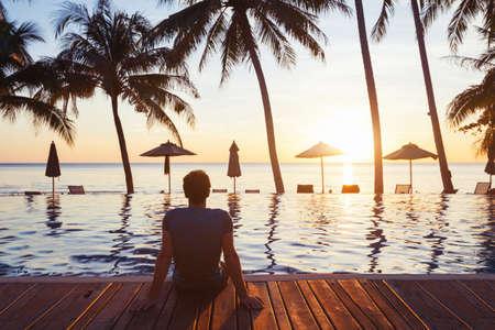 해변에서 휴식, 수영장 근처의 고급 호텔에서 아름다운 일몰을 즐기고있는 젊은이 스톡 콘텐츠
