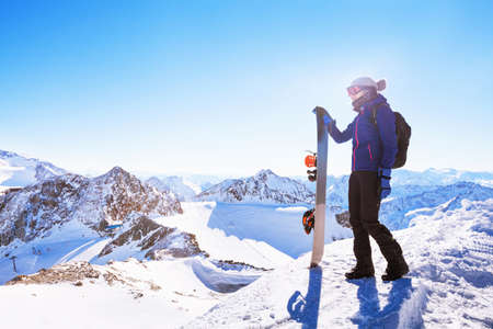 young woman with snowboard, winter holidays in Austria, panoramic mountain landscape of Alps