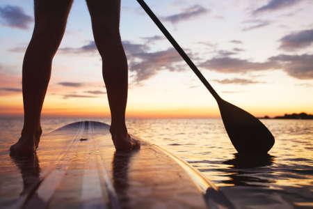 パドルボード、ビーチに立っている足とパドルのクローズ アップ