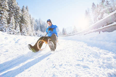 sledging people: sleigh, winter holiday snow activity, young man having fun sledding Stock Photo