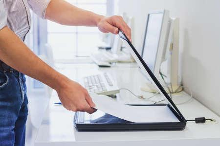 met behulp van scanner in kantoor of bibliotheek, close-up van handen documenten scannen
