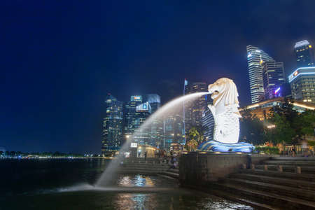 SINGAPORE - SEPTEMBER 06 2016: Night scene of illuminated Merlion fountain and modern business buildings on background Stock Photo - 77867239