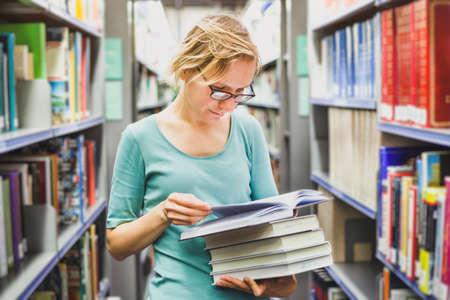 student meisje in de bibliotheek lezen van boeken, onderwijs concept Stockfoto