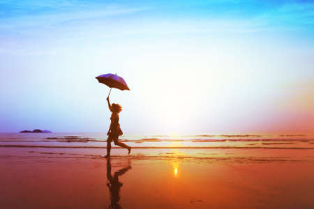 silhouette of happy carefree girl with umbrella jumping on the beach at sunset, freedom and joy concept