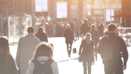 abstract crowd of people walking on the street, unrecognizable silhouettes with back light