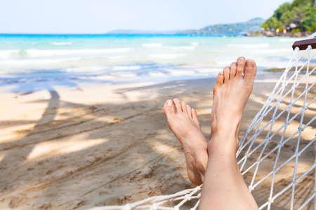 strandvakanties achtergrond, vakantie en ontspanning concept, voeten van persoon in hangmat Stockfoto