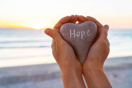 希望の概念、両手で石上に書かれた言葉で