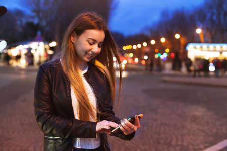 Jonge vrouw met behulp van smartphone op straat 's nachts en glimlachen Stockfoto - 82435091