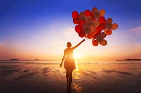 inspiration, joy and happiness concept, silhouette of woman with many flying balloons on the beach 免版税图像 - 82435092