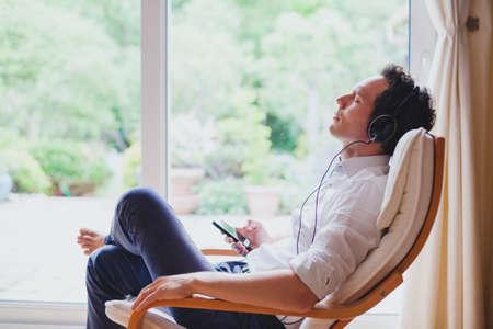집에서 편안한 음악을 듣고, 현대 밝은 실내에 갑판 의자에 앉아 헤드폰에서 편안한 남자 스톡 콘텐츠 - 82435105