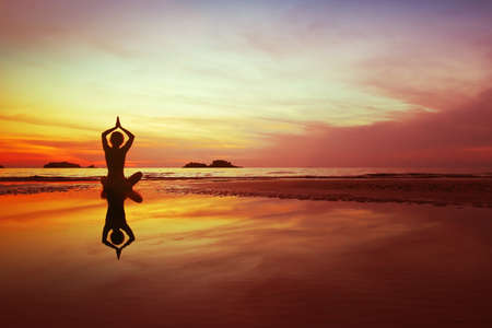 yoga practice on the beach at sunset, woman silhouette on beautiful nature landscape background, meditation concept