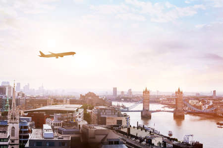 travel to London by flight, airplane in the sky over Tower Bridge
