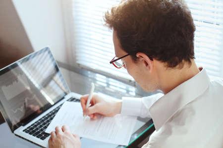 zakenman manager werken met financiële gegevens en papieren in het kantoor, schrijven verslag Stockfoto