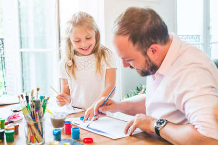 father and daughter painting watercolor drawings together at home