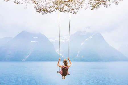 dream concept, beautiful young woman on the swing in fjord Norway, inspiring landscape