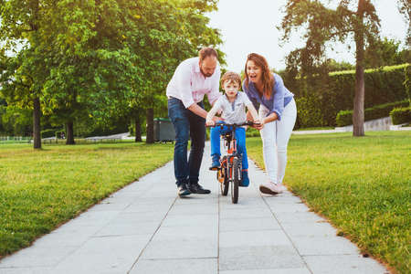 parents helping child to learn how to ride bicycle