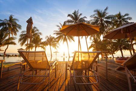 two deckchairs near swimming pool at sunset in luxury beach hotel on tropical island