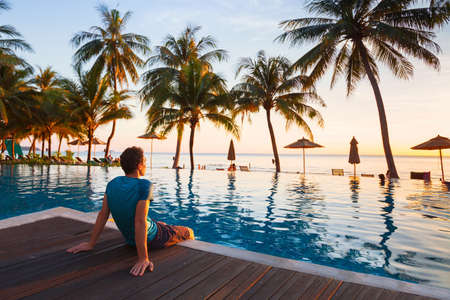 Frohe Feiertage in schönem Strandhotel bei Sonnenuntergang, Mann sitzt in der Nähe Schwimmbad und entspannend
