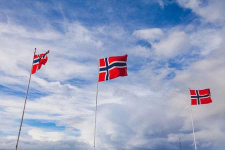 노르웨이, 푸른 하늘 배경에 흔들며 노르웨이 플래그 스톡 콘텐츠