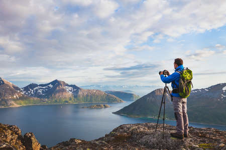 landscape photographer working with tripod and dslr camera in beautiful wild nature, standing with backpack on top of mountain Imagens