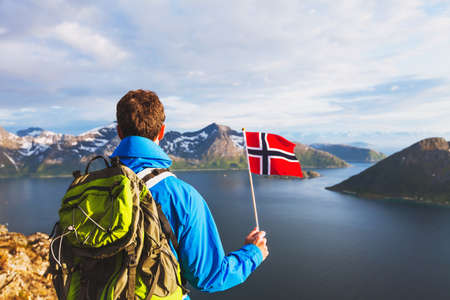 travel to Norway, hiker traveler with backpack holding norwegian flag and looking at beautiful fjord landscape