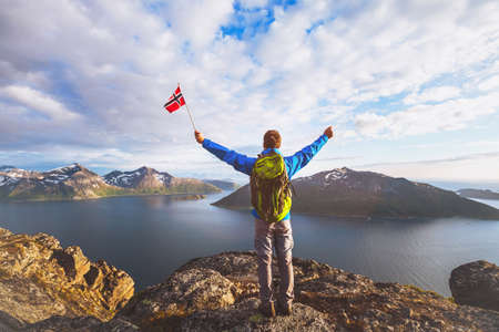 travel to Norway, happy tourist hiker with backpack standing on the top of mountain and holding norwegian flag