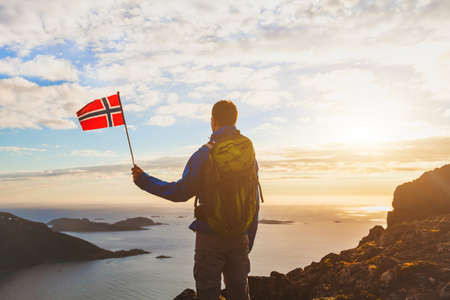 hiking in Norway, silhouette of tourist with norwegian flag looking at beautiful fjord nature with light of midnight sun